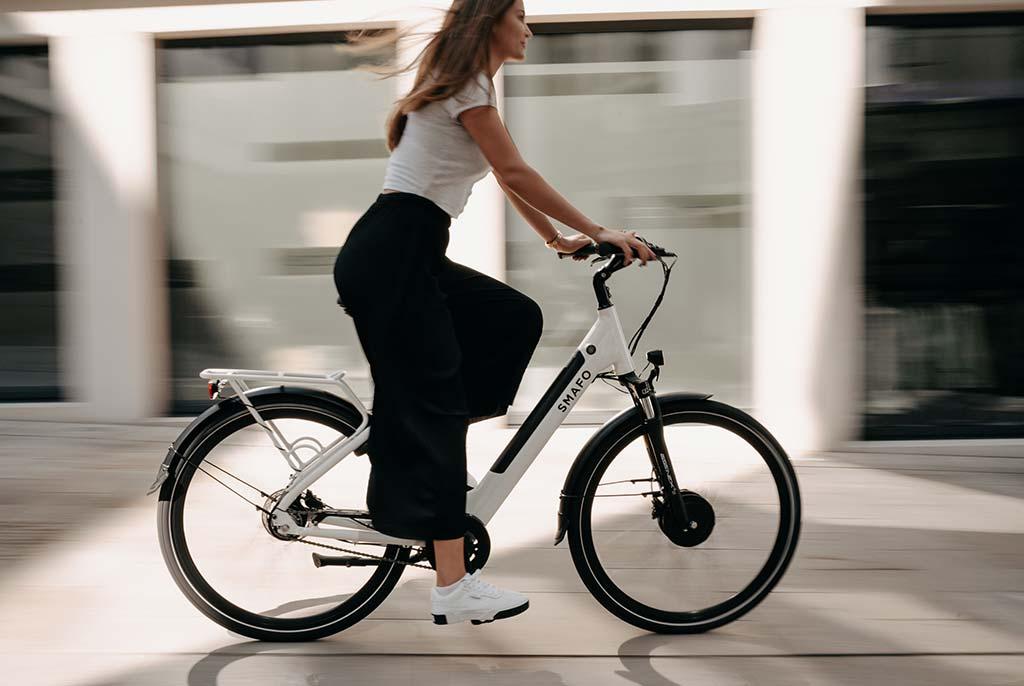 Eine junge Frau fährt auf einem schicken E-Bike zur Arbeit.