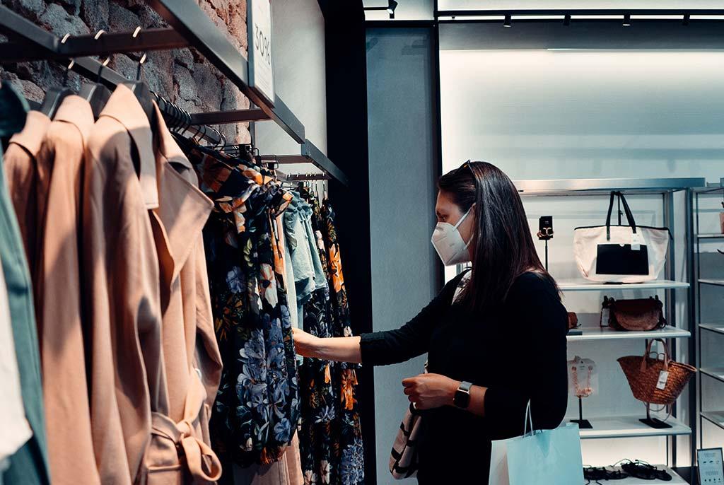 Eine Frau in einer Boutique. Die Boutique ist klein aber fein.