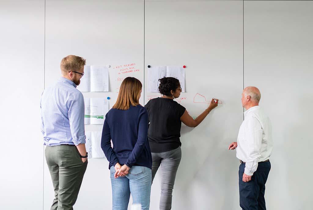 Junge Mitarbeiter und ihr Chef an einem Wandplakat.